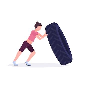 Sportfrau, die einen reifen umdreht, der harte übungsmädchen tut, die im weißen crossfit-training des gesunden cross-trainings des fitnessraums trainieren, weißer hintergrund
