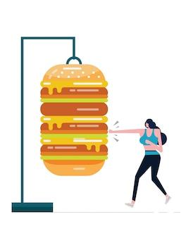 Sportfrau, die großen hamburger boxt. kämpfen sie ungesundes nahrungsmittelkonzept.