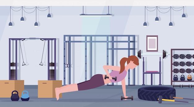 Sportfrau, die hanteln macht plankenübungsmädchen, das gewicht hebt, das im fitnessstudio crossfit-training des gesunden lebensstils-konzept-flachen modernen gesundheitsclub-studio-innenraums horizontal trainiert
