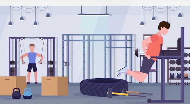 Sportler, die übungen auf parallelbarren-trainingsgeräten machen jungs, die im crossfit-training des gesunden fitness-lifestyle-konzepts des modernen gesundheitsclubs studio interieur trainieren