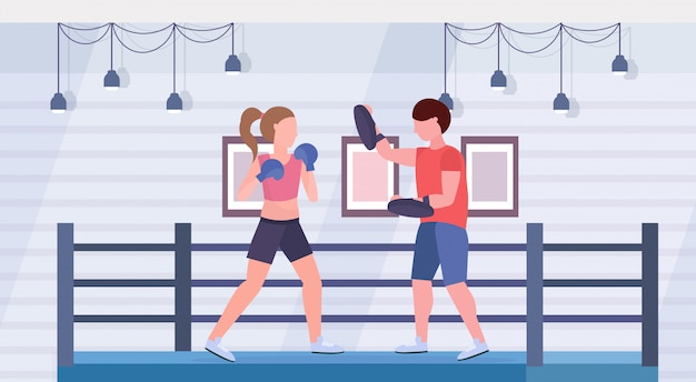Sportlerin boxer, die boxübungen mit männlichem trainer-mädchen-kämpfer in blauen handschuhen übt, die kampfringarena-innenkonzept des gesunden lebensstils flach horizontal ausübt