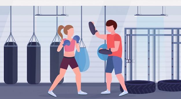 Sportlerin boxer macht boxübungen mit personal trainer mädchen kämpfer in blauen handschuhen kampf club mit boxsäcken fitnessstudio interieur gesunden lebensstil konzept
