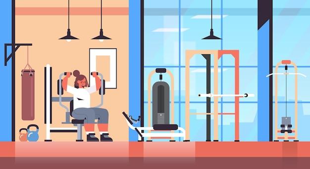 Sportlerin, die auf trainingsapparatmädchen trainiert, das körperliche übungen ausarbeitet, die das moderne fitnessstudio-interieur des gesunden lebensstilkonzepts ausarbeiten