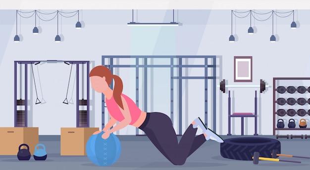 Sportliche frau, die crossfit-übungen mit medizin leder ball mädchen training cardio workout-konzept moderne turnhalle gesundheit studio club interieur horizontal in voller länge macht