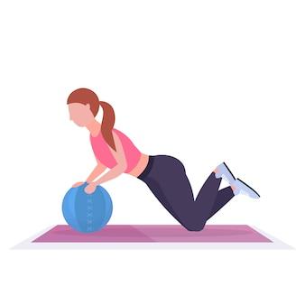 Sportliche frau, die crossfit-übungen mit medizin-lederballmädchen-training im fitnessstudio cardio-workout-konzept des gesunden lebensstils weißer hintergrund in voller länge macht