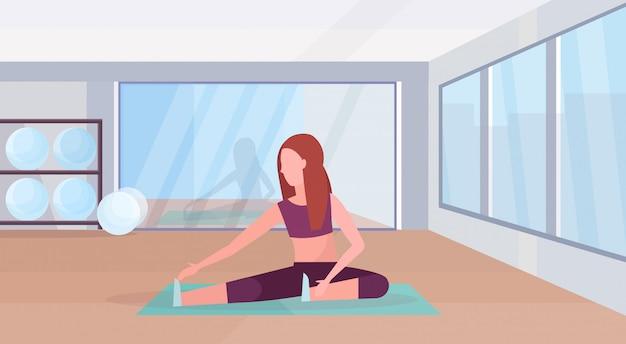 Sportliche frau, die dehnungsübungen mädchen trainiert im fitnessstudio aerobic-training gesunde lebensweise konzept flache moderne health club studio interieur horizontal in voller länge