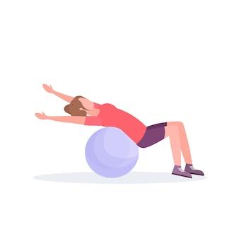 Sportliche frau, die fitnessballmädchen liegt, das übungs-training im aeroben pilates-workout des gesunden lebensstils des flachen weißen hintergrunds trainiert
