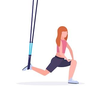 Sportliche frau, die kniebeugenübungen mit aufhängung fitnessgurte elastisches seil mädchen training im fitnessstudio crossfit cardio workout gesunden lebensstil konzept weißen hintergrund in voller länge macht