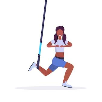 Sportliche frau, die kniebeugenübungen mit aufhängungsfitnessbändern elastisches seilmädchentraining im fitnessstudio crossfit cardio workout konzept weißen hintergrund in voller länge macht