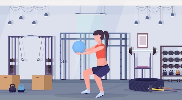 Sportliche frau, die kniebeugenübungen mit fitnessballmädchen trainiert, das aerobes training des gesunden lebensstils des modernen fitnessraums des innenraums flach horizontal horizontal trainiert