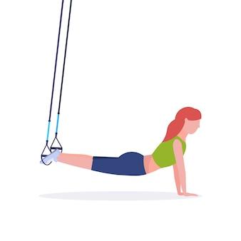Sportliche frau, die übungen mit aufhängung fitnessgurte elastischen seil mädchen training im fitnessstudio crossfit cardio workout gesunden lebensstil konzept weißen hintergrund in voller länge macht