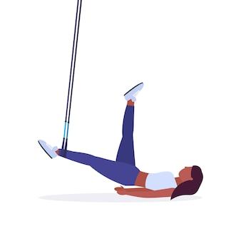 Sportliche frau, die übungen mit aufhängung fitnessgurte elastischen seil mädchen training im fitnessstudio crossfit cardio workout konzept weißen hintergrund voller länge macht