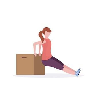 Sportliche frau, die übungen mit hölzernem kastenmädchentraining im weißen hintergrund des gesunden aeroben trainingskonzeptes des gymnastik-aerobic-trainings macht