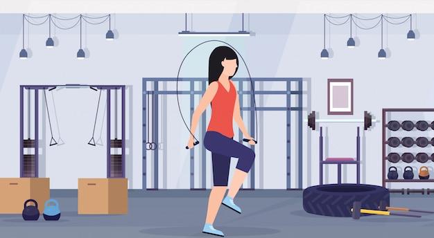 Sportliche frau, die übungen mit springseilmädchen-training im aeroben workout des gesunden lebensstils des fitnessraums des flachen modernen gesundheitsklubstudio-innenraums horizontal macht