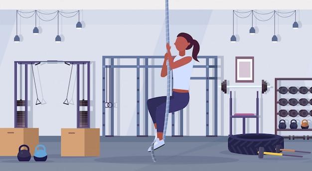 Sportliche frau macht seilklettern übung afroamerikaner mädchen training cardio crossfit workout-konzept moderne turnhalle gesundheit studio club interieur horizontal flach in voller länge