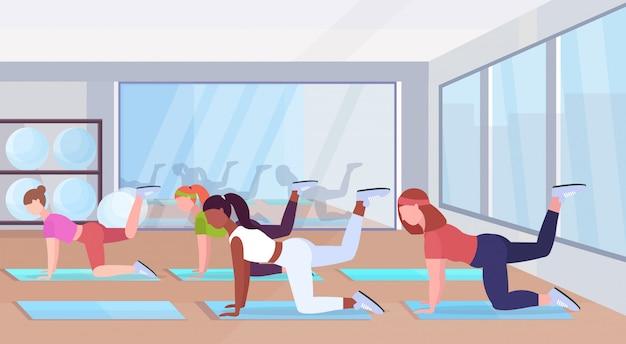 Sportliche frauen, die fitnessübungen auf yogamattenmischungsrassenmädchen machen, die im fitnessstudio trainieren gesundes lebensstilkonzept flaches modernes gesundheitsklubstudio innen horizontal