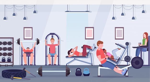 Sportliche leute, die übungen männer frauen, die zusammen an trainingsgeräten im fitnessstudio trainieren, trainieren gesunde lebensweise konzept modernen health club studio interieur horizontal
