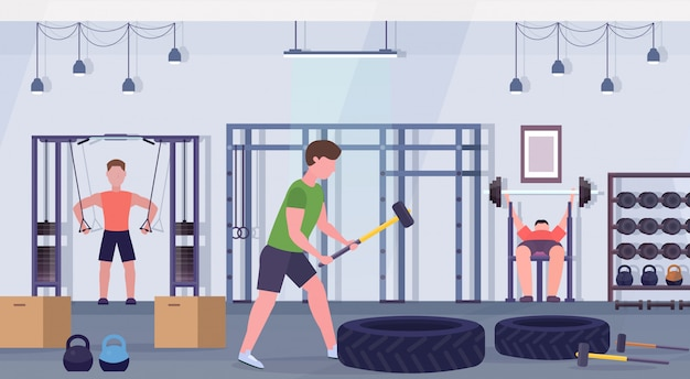 Sportliche leute, die übungen männer tun, die zusammen auf trainingsgeräten im fitnessstudio crossfit workout gesunden lebensstil konzept modernen health club studio interieur horizontal trainieren