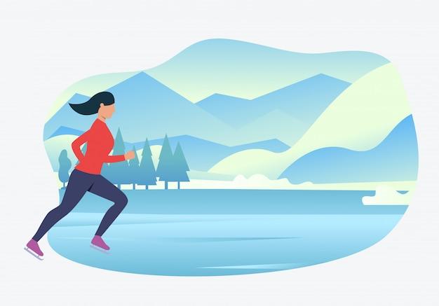 Sportlicher fraueneislauf mit schneebedeckter landschaft im hintergrund