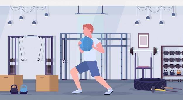 Sportlicher mann, der crossfit-übungen macht, die mit medizin-lederball-typ-trainings-cardio-trainingskonzept laufen. modernes fitnessstudio-gesundheitsstudio-club-interieur horizontal in voller länge