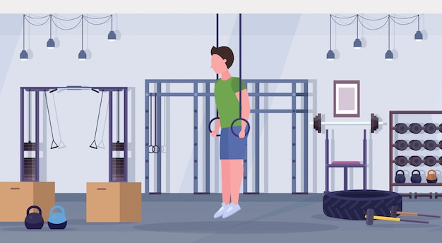 Sportlicher mann, der ring-dips-übungen mit gymnastikringen macht, trainiert cardio-crossfit-trainingskonzept
