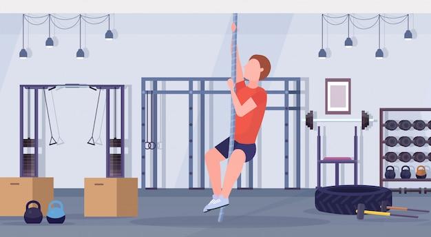 Sportlicher mann, der seilklettern übung kerl training cardio crossfit workout-konzept moderne turnhalle gesundheit studio club interieur horizontal flach in voller länge