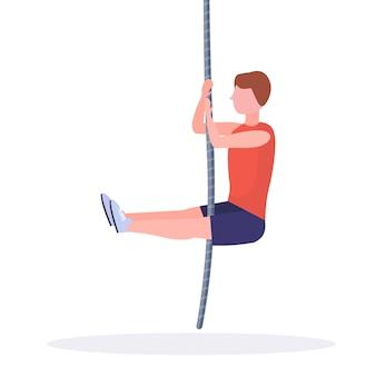 Sportlicher mann, der seilklettern übung kerl training im fitnessstudio cardio crossfit workout gesunden lebensstil konzept weißen hintergrund voller länge tut