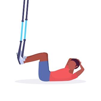 Sportlicher mann, der sit-ups bauchübungen mit aufhängung fitnessgurte elastischen seil kerl training im fitnessstudio crossfit cardio workout konzept weißen hintergrund voller länge macht