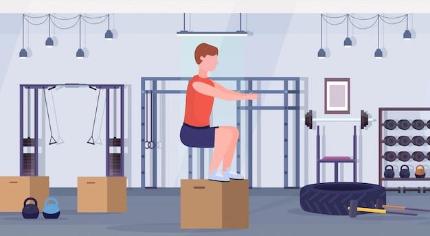 Sportmann, der box squat übungen kerl springt, der im fitnessstudio crossfit gesunden lebensstil konzept modernen health club studio interieur horizontal trainiert