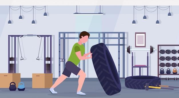 Sportmann, der einen reifen umdreht, der harte übungs-kerl tut, der im crossfit-training des gesunden fitness-lifestyle-konzepts des modernen gesundheitsclubs studio interieur horizontal trainiert