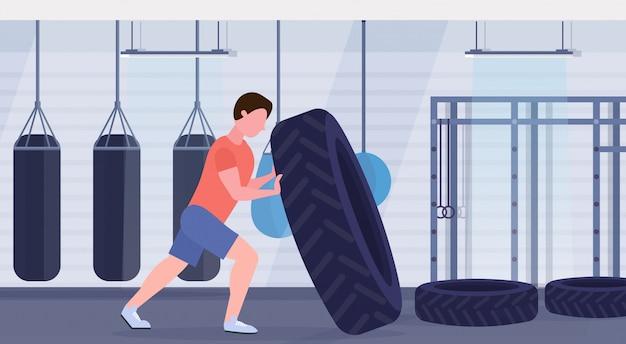 Sportmann, der einen reifen umdreht, der harte übungs-kerl tut, der im fitnessstudio mit boxsäcken crossfit-training des gesunden lebensstils des modernen gesundheitsclubs interieur horizontal trainiert