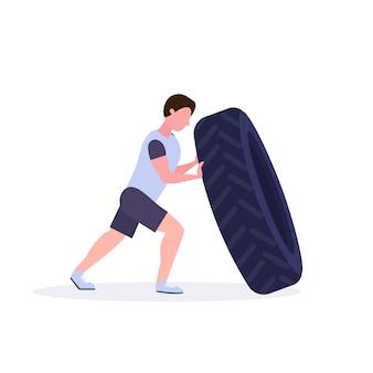 Sportmann, der einen reifen umdreht, der harte übungs-kerl tut, der im weißen crossfit-training des gesunden hintergrundkonzeptes des gesunden cross-trainings trainiert