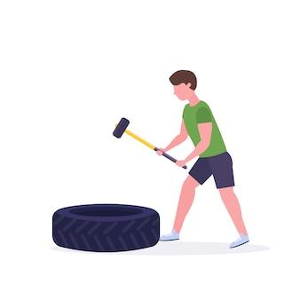 Sportmann, der großen reifen mit hummer trifft, der harte übungsjunge tut, der im weißen crossfit-training des gesunden hintergrundkonzeptes des gesunden crossout-trainings trainiert