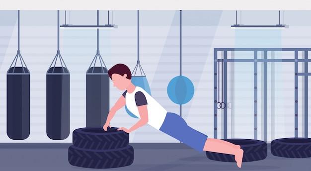 Sportmann, der push-up-übung auf reifen bodybuilder tut, der im fitnessstudio hartes training des gesunden lebensstils konzept flachen modernen crossfit healht club interieur horizontal trainiert
