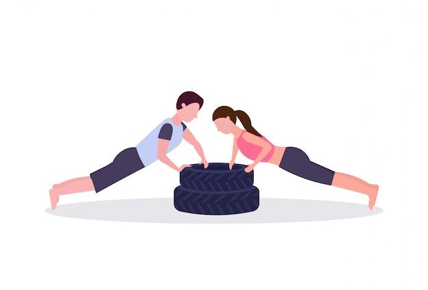 Sportpaar, das liegestützübung auf reifenmannfrau tut, die im fitnessstudio crossfit-training des gesunden lebensstilkonzepts des weißen hintergrunds horizontal arbeitet