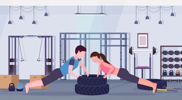Sportpaar, das liegestützübung auf reifenmannfrau zusammenarbeitet, die zusammen crossfit-training des gesunden lebensstils des modernen fitnessraums ausrichtet, flache horizontale innenausstattung