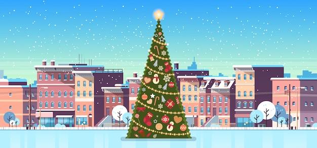 Stadtgebäude bringt winterstraße mit verzierter kiefer für weihnachten unter