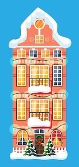 Stadthaus mit schnee bedeckt. gebäude in feiertagsverzierung. weihnachtsbaum-fichte, kranz. frohes neues jahr dekoration. frohe weihnachtsfeiertage. neujahrs- und weihnachtsfeier. flache vektorillustration