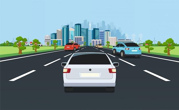 Stadtverkehr auf der autobahn mit panoramablick auf die moderne stadt mit wolkenkratzern und vororten auf hintergrund bergen, hügeln. straße mit autos, die in die stadt führen.