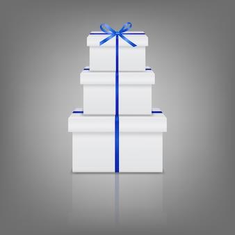 Stapel von drei realistischen weißen geschenkboxen mit blauem band und schleife
