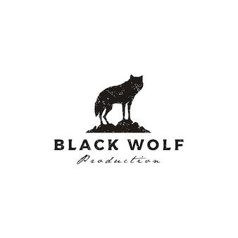 Stehender schwarzer wolfsfuchs-hunde-kojoten-schakal auf dem felsen rustikales weinleseschattenbild-retro-hipster-logo-design
