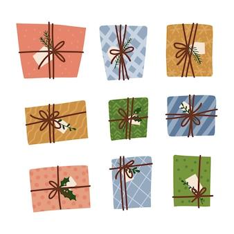 Stellen sie ein, wenn weihnachtsgeschenkbox mit einem seil umwickelt ist, das mit zweigen kiefernblättern auf weißem hintergrund verziert ist ...