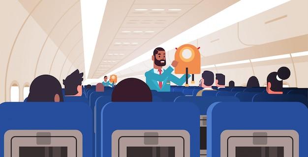 Steward erklärt den passagieren, wie man eine schwimmweste in einer notsituation verwendet. afroamerikaner flugbegleiter sicherheitsdemonstrationskonzept modernes flugzeugbrett interieur horizontal flach