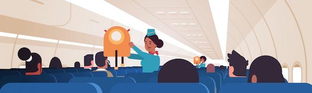 Stewardess erklärt für passagiere, wie man schwimmweste in notsituation verwendet afroamerikaner flugbegleiter sicherheitsdemonstrationskonzept modernes flugzeugbrett interieur horizontal