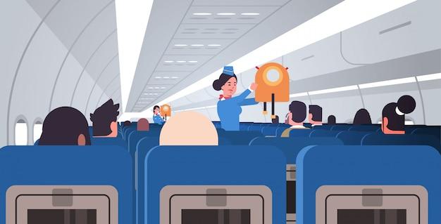 Stewardess flugbegleiterin erklärt für passagiere, wie man eine schwimmweste in einer notsituation verwendet. sicherheitsdemonstrationskonzept modernes flugzeugbrett interieur horizontal flach