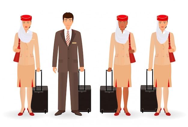 Stewardess und muslimische piloten. wirkliche leute des fliegenteams, die in der uniform mit koffern stehen.