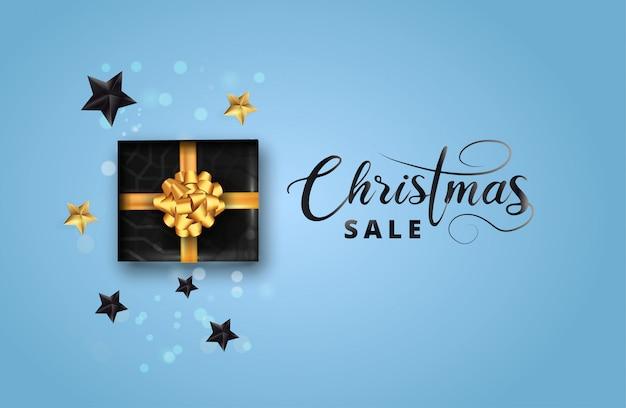 Stilvolle verkaufsbeschriftung der frohen weihnachten, schwarze mustergeschenkbox herum auf blauem bokeh. kann als poster, banner oder vorlage verwendet werden.