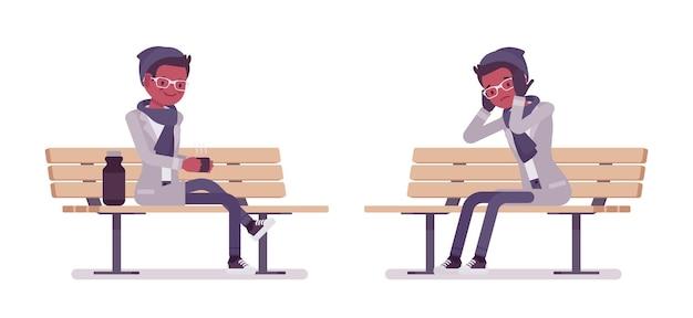Stilvoller junger schwarzer mann, der auf bank sitzt, die herbstkleidungsillustration trägt