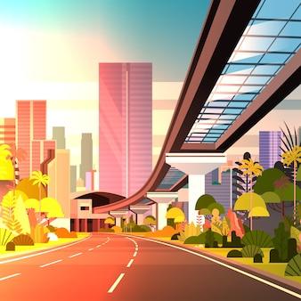 Straße zur großstadt mit wolkenkratzern und moderner sonnenuntergang-stadtbild-bahnansicht