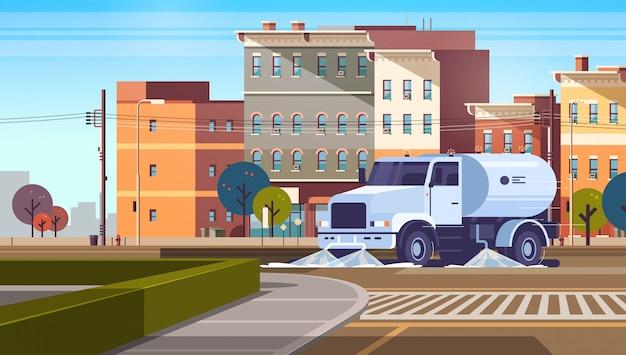Straßenkehrwagen auf kreuzung, die asphalt mit wasser-industriefahrzeug wäscht